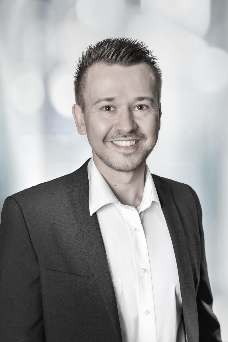 Sympathisch lächelnder Mann im Anzug als Profilbild für den Übersetzer und Dolmetscher Thomas Baumgart