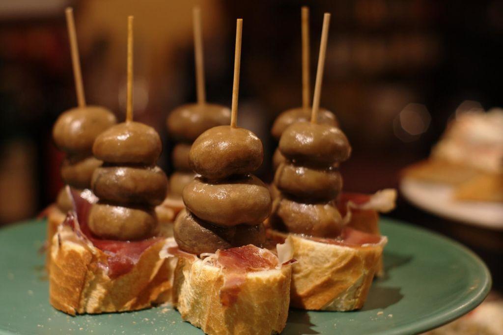 Ein pincho bestehend aus einer Brotscheibe, Schinken und marinierten Champignons – und dem charakteristischen Holzstäbchen
