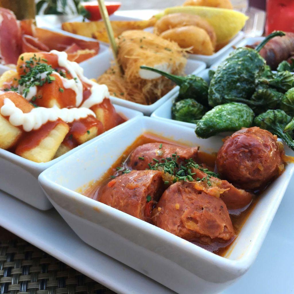 Tapa-Variation: Kartoffeln mit scharfer Soße und Mayonnaise, Chorizo, Bratpaprika, Schinken, Datteln im Speckmantel ...