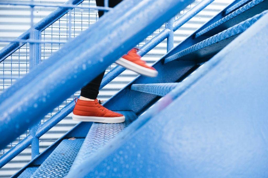 Zwei rote Sportschuhe, die Treppen aufsteigen